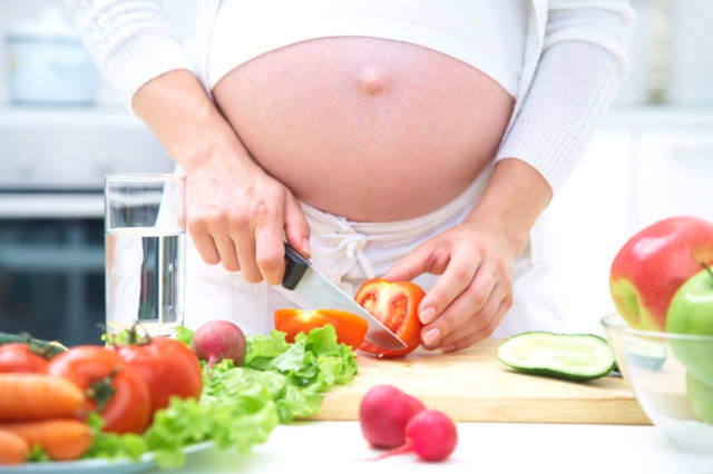 Pregnant woman in kitchen making salad