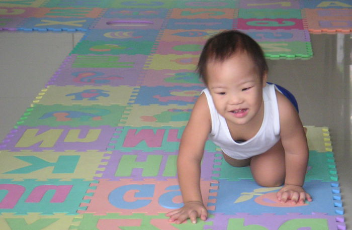 baby with special needs crawling on the floor