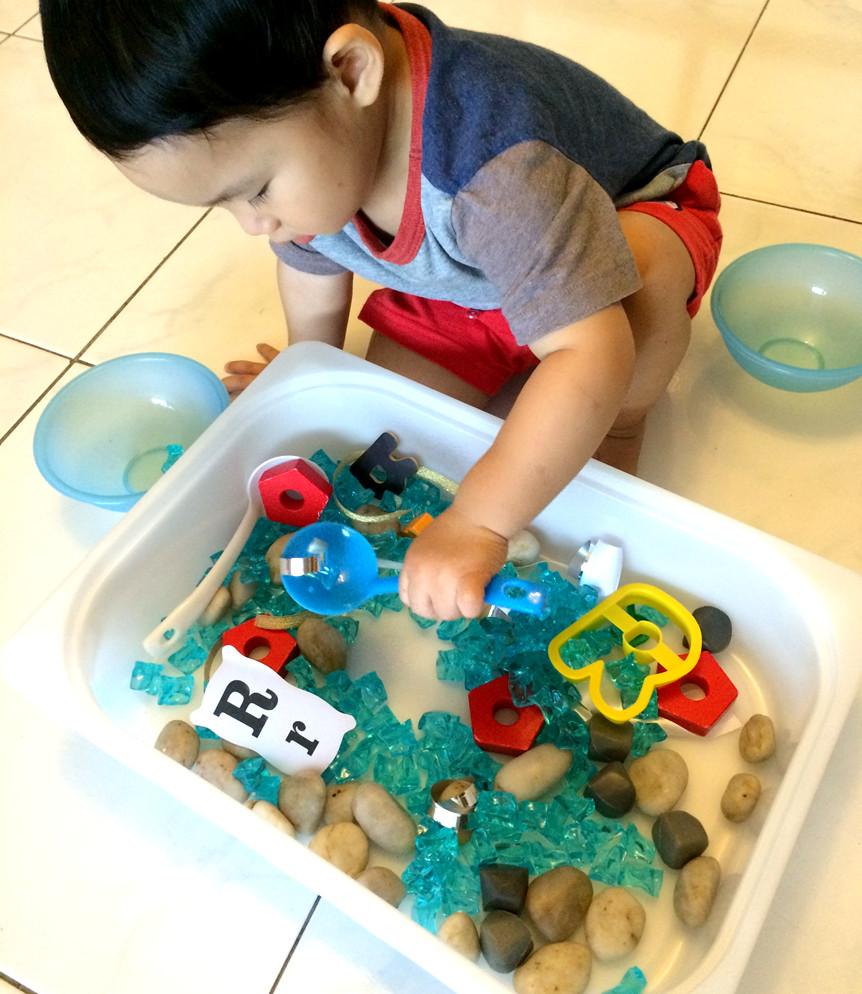 child exploring sensory bin