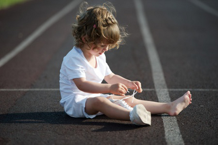 girl learning to tie shoelaces.
