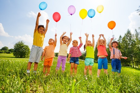 Happy kids flying balloons