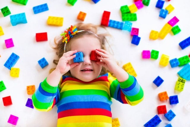 little girl playing with construction toy blocks