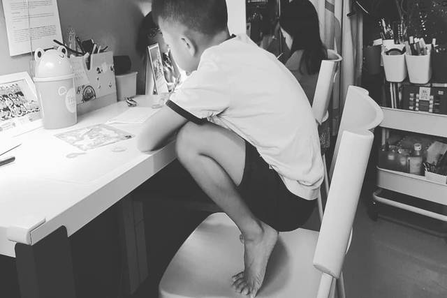 Child squatting at desk