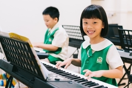 Kinderland student playing piano